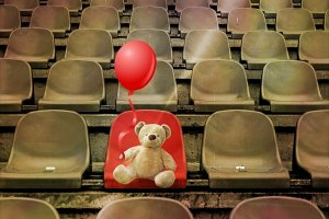 teddy bear seated in a stadium with red balloon